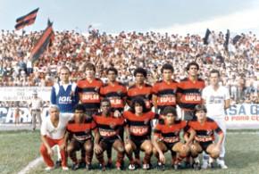 """Ferroviário Atlético Ituano (1985) perfilado para um jogo no Estádio Municipal Dr. Novelli Júnior. Na foto aparece o artilheiro Django (quarto da esquerda para a direita, agachado) e, ao fundo, a frenética torcida do """"Galo Ituano"""", daquela época - Arquivo Campo&Cidade"""